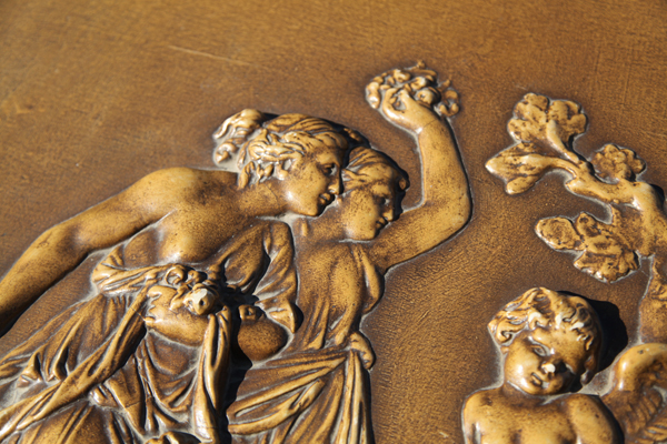 High relief carvings of grecian ladies and cherub on piano lid