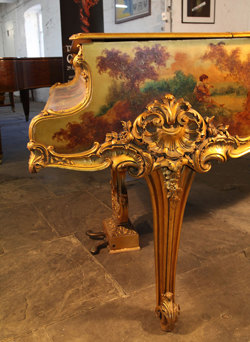 Pleyel Piano Cheek Detail Featuring Oil Painting of a Boy Playing a Musical Instrument in the Countryside. Ornately Carved Giltwood Leg with Scroll Foot