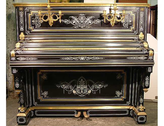 A Debain et Cie upright piano with an ebonised case. Intricately inlaid with ivory. Case covered with brass ormulu mounts