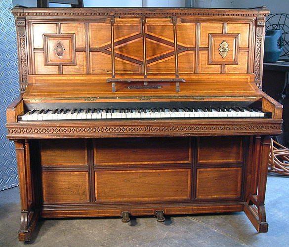 An 1875, Hopkinson upright piano with a polished, rosewood case, inlaid with a variety of woods and carved detail.