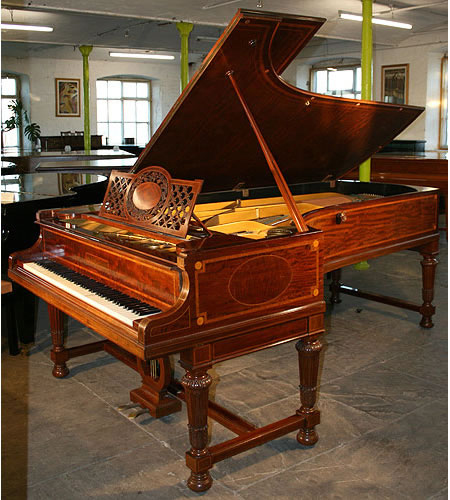 An antique, inlaid Bechstein Model E Grand with a polished, fiddleback mahogany case. Cabinet features satinwood and boxwood stringing inlay