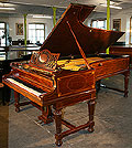 An antique Bechstein Model E Grand with a polished, fiddleback mahogany case inlaid with stringing and boxwood detail. 