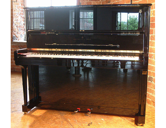 A brand new Steinway Model K upright piano with a black case and polyester finish