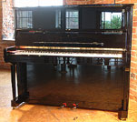 Piano for sale. A brand new Steinway Model K Upright with a black case and polyester finish.