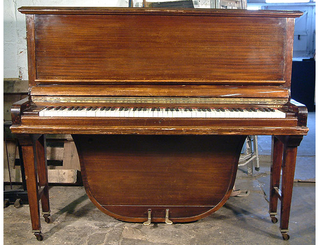 A Morley upright grand piano with a polished, mahogany case