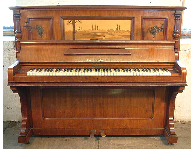 A Cahn & Cahn upright piano with a polished rosewood case, Ibeautifully inlaid with a japanese landscape