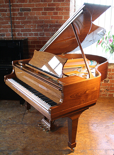A brand new, Steinway Model M grand piano with a walnut case and polyester finish