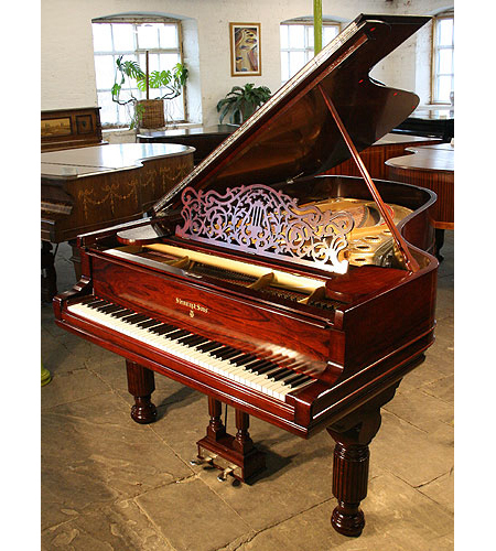 An antique Steinway Model B grand piano with a polished, rosewood case.