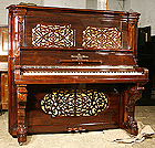A restored Steinway upright piano with a polished, rosewood case and ornate fretwork. 