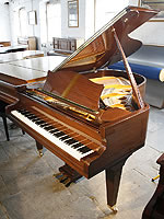 A Bechstein Model M grand piano with a polished, mahogany case.