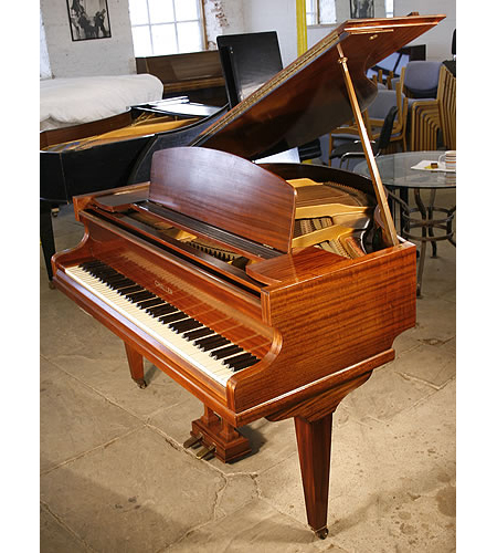 A 1936, restored, Challen baby grand piano with a mahogany case