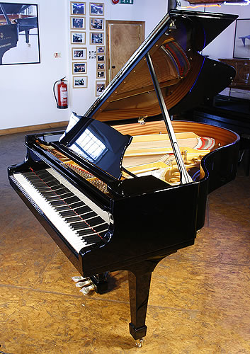 A brand new Steinway Model M grand piano with a black case and spade legs