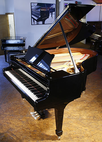 A brand new Steinway Model O grand piano with a black case and spade legs