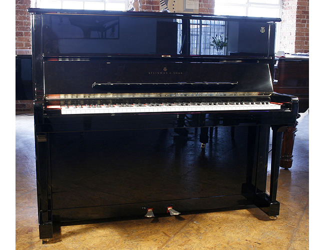 A Brand New Steinway Model V upright piano with a black case