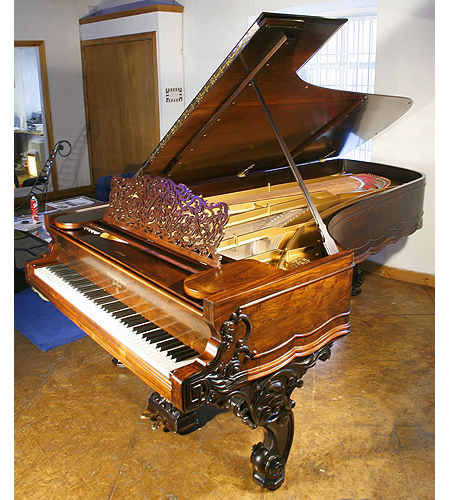 An 1870, antique Steinway concert grand piano with a rosewood case and heavy carved legs
