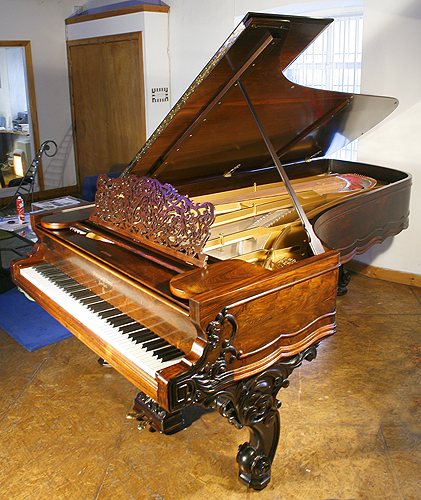 An ornately carved, 1870, Steinway concert grand piano with a rosewood case