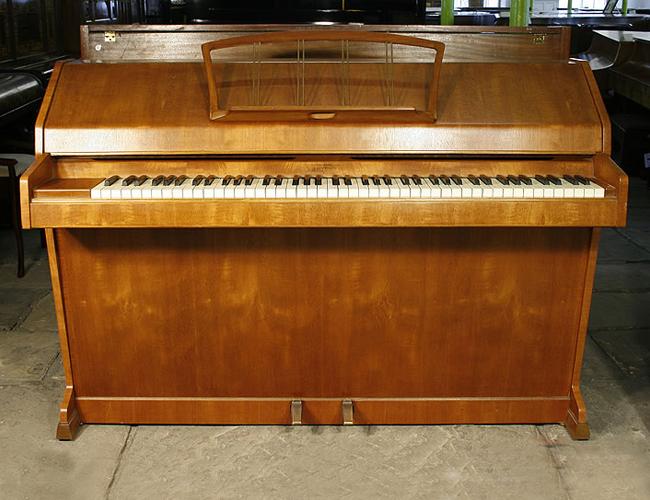 An Eavestaff mini piano with a polished, teak case