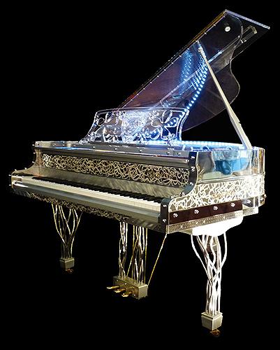 """杰瑞庞斯(Gary Pons)型号 SY160 三角钢琴,使用特殊透明材质,安装有LED灯,可以通过外壳看到内部击弦机的结构与活动原理,这架钢琴来自于""""Plexart""""展会,每一架都有单独的编号,并且由设计者签名,外壳有多种造型可供选择,每台琴的LED设计均是独一无二的艺术设计,提供订购服务"""