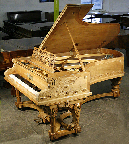 An intricately carved Bechstein Model C grand piano with an ornately carved, walnut case. Cabinet features carvings of two swans on the water on piano cheeks. Twisted around the rear piano leg is a two-headed serpent dragon. Based on themes found in Richard Wagner's great Ring Cycle works