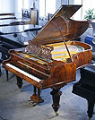 An antique Bechstein Model V grand piano with a polished, burr walnut case.