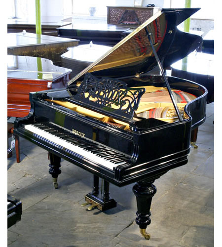 A restored, Berdux grand piano with a polished, black case and turned legs