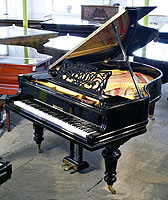 A restored, Berdux grand piano with a polished, black case and turned legs. Music desk features an art nouveau cut-out design with sinuous tendrils and the Berdux name.