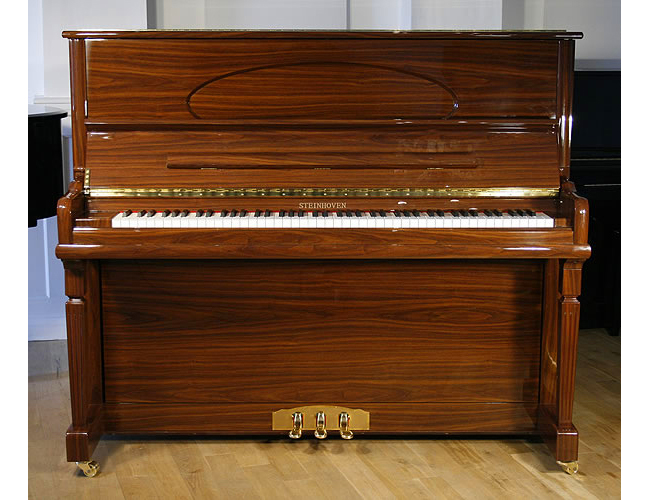 A brand new Steinhoven model 128 upright piano with a walnut case and polyester finish