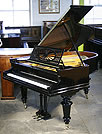 An antique, restored Bechstein Model A1 grand piano with a black case. 