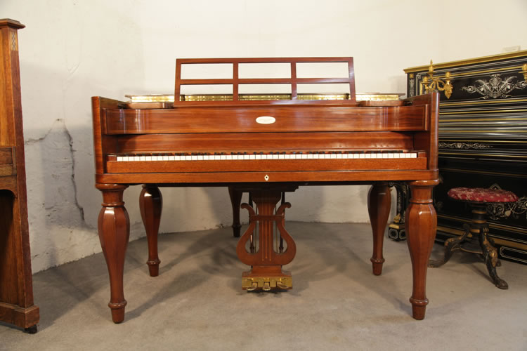 Front view of this Steinway model M piano showing the five baluster legs, high piano cheeks, open work music desk and traditionally shaped piano lyre.