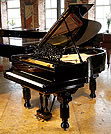 An antique, Steinway Model A grand piano with a polished, black case. 