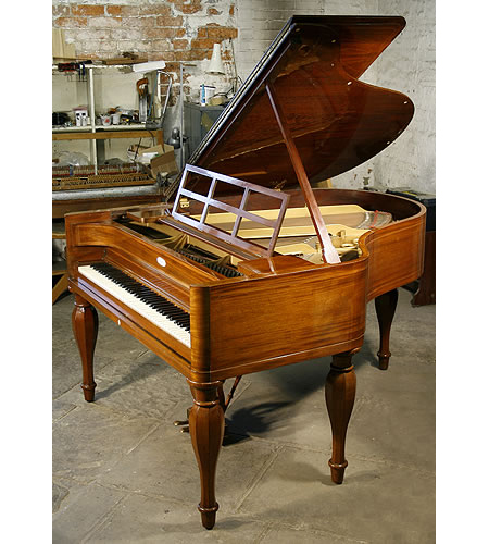 A 1926, Steinway Model M grand piano with a french polished, mahogany case and stringing inlay. Piano has five baluster legs. Design based on the first piano made by Heinrich Steinweg in 1836