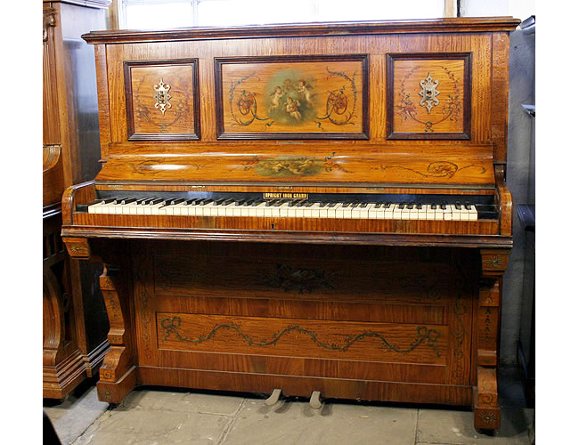 A Payne upright piano with a hand-painted satinwood case. Hand-painted with musical instruments, cherubs, flowers and swags
