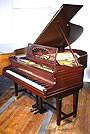 An antique, Bechstein Model A grand piano with a polished, mahogany case and gate legs.
