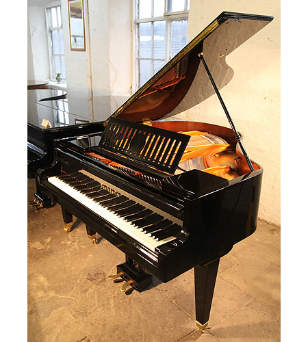 A 1936, restored, Bosendorfer baby grand piano for sale with a black case, slatted music desk and square, tapered legs