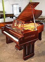 A 1916, Arts and Crafts Ibach grand piano with a polished, mahogany case.