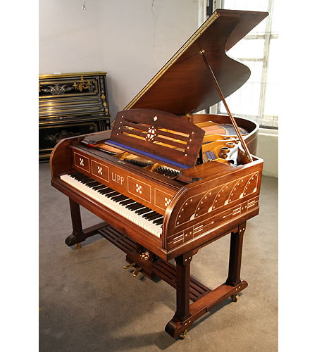 An Arts and Crafts, Lipp grand piano for sale with a mahogany case inlaid with geometric designs. Case features ornate brass hinges and slatted cross stretcher