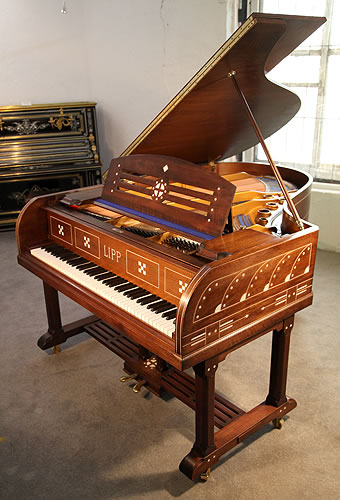 An Arts and Crafts, Lipp grand piano for sale with a mahogany case inlaid with geometric designs. Case features ornate brass hinges and slatted cross stretcher.