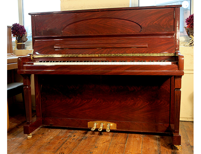 A brand new Steinhoven model HG126 upright piano with a mahogany case and polyester finish. Piano features a soft fall mechanism and brass footplate