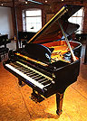 A 1980,  Steinway Model B grand piano with a black  case. 
