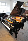 A restored Bechstein Model A grand piano with a polished, black case. 