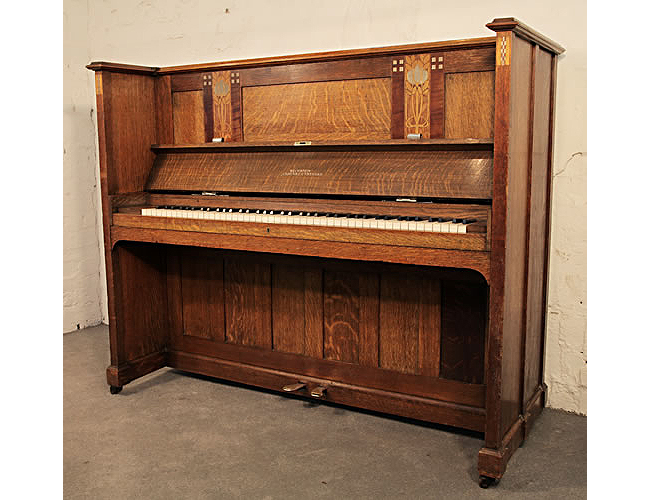 A Bechstein model IV upright pano with an Arts and Crafts oak case. Case features inlaid panels of Glasgow style stylised flowers in pewter and fruit woods