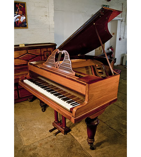An antique, 1899, Broadwood grand piano with a polished, rosewood case, turned legs and elegant, filigree music desk