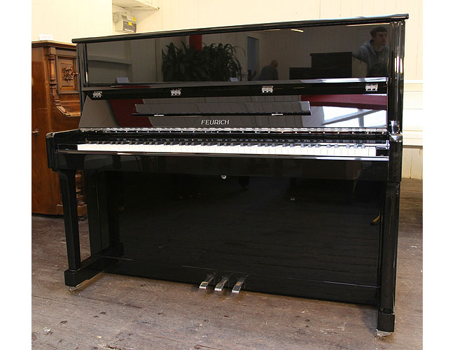 A Brand New Feurich Model 122 upright piano with a black case and chrome fittings