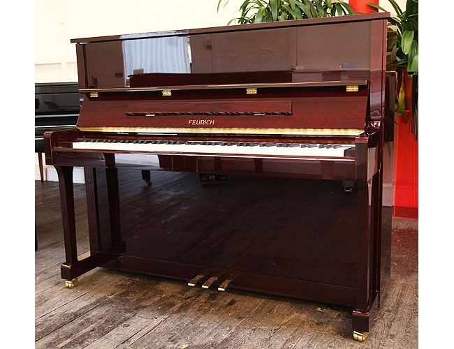 A Brand New Feurich Model 122 upright piano with a Bordeaux Gloss mahogany case and brass fittings