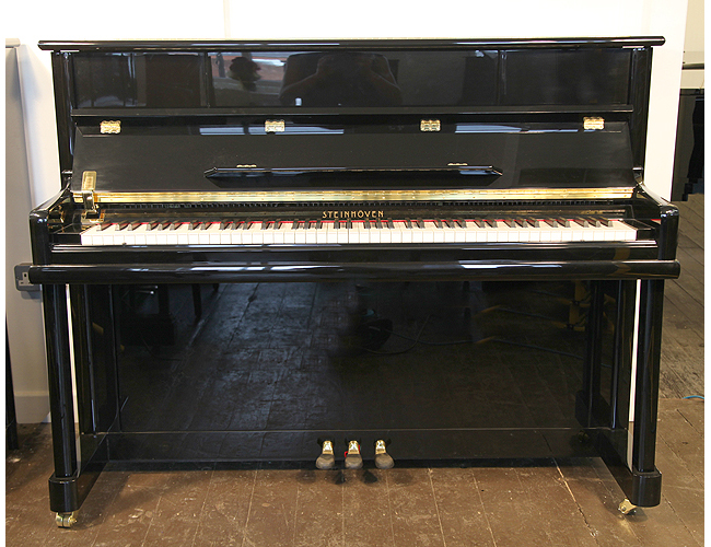 A brand new Steinhoven model 112 upright piano with a black case and polyester finish.