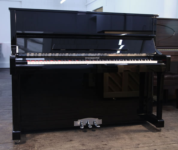 A brand new Steinhoven model 121 upright piano with a black case