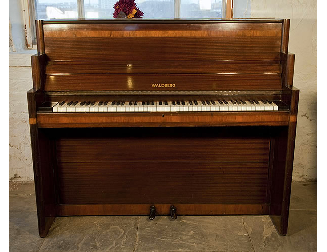 An Art-Deco style, Waldberg upright piano with a polished, mahogany case. Cabinet features geometric styling and banded inlay