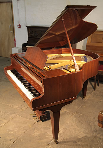 A Welmar baby grand piano with a polished, mahogany case and square, tapered legs