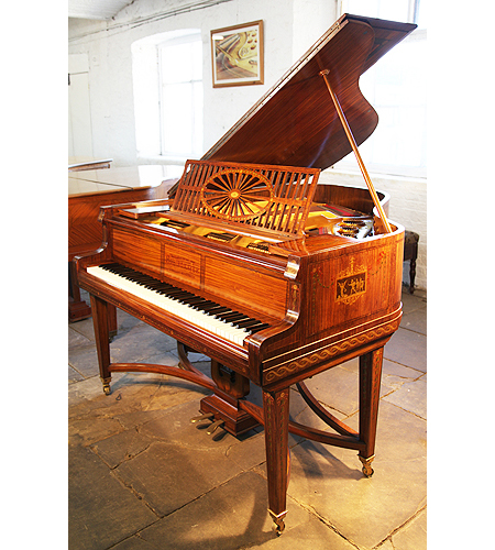 An  1899, Schiedmayer grand piano for sale with a satinwood case. Cabinet features crossbanding and boxwood stringing accents and is hand painted in romanesque designs with cherubs, soldiers and dancing ladies