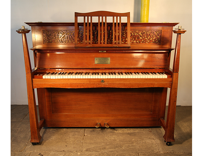 A 1901, Arts and Crafts Bechstein upright pano with a mahogany case. Case features sculptural candlesticks, a fretwork panel and ornate brass hinges